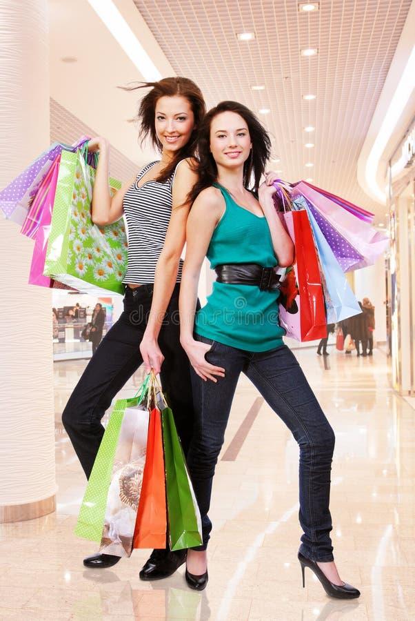 Jonge volwassen meisjes met het winkelen zakken bij winkel stock afbeelding