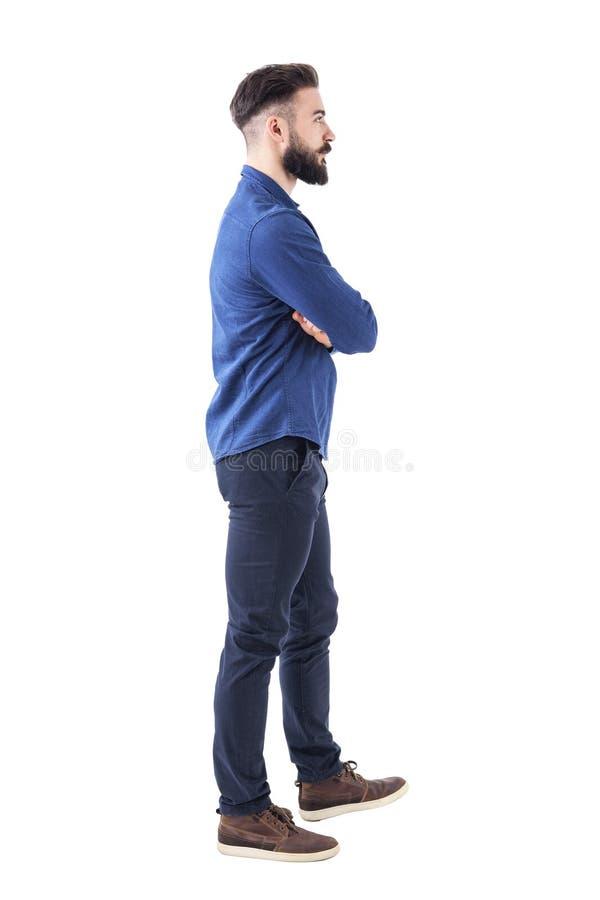 Jonge volwassen mens in blauw denimoverhemd die en met gekruiste wapens er vandoor gaan kijken stock afbeeldingen
