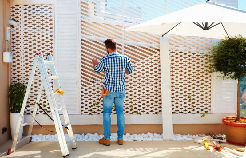 Jonge volwassen mens die houten pergolamuur bouwen op de streek van het dakterras stock afbeeldingen