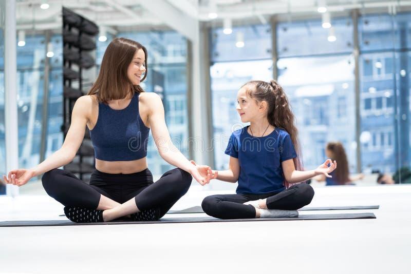 Jonge volwassen moeder en weinig dochter die samen yoga uitoefenen royalty-vrije stock afbeelding