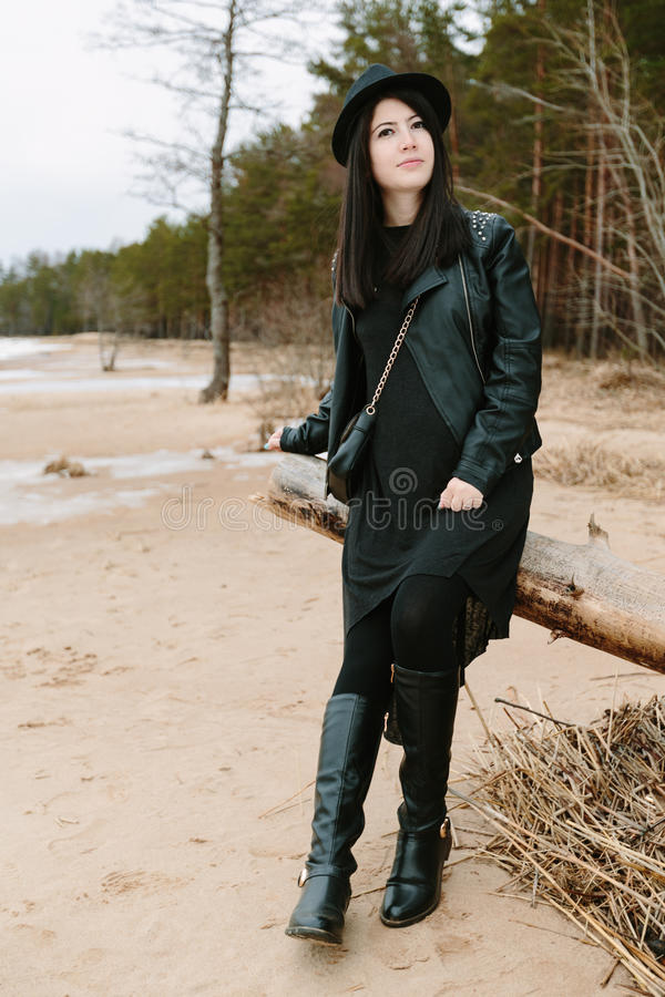 Jonge volwassen mooie donkerbruine vrouw in zwarte kleding en zwarte hoed stock afbeelding