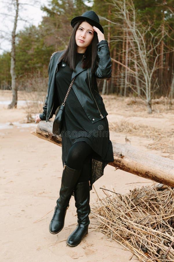 Jonge volwassen mooie donkerbruine vrouw in zwarte kleding en zwarte hoed royalty-vrije stock fotografie