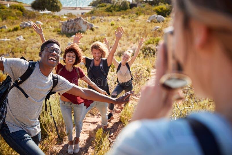 Jonge volwassen vrienden die en foto's van elkaar stellen nemen tijdens een stijgingshelling op een kustweg stock afbeeldingen
