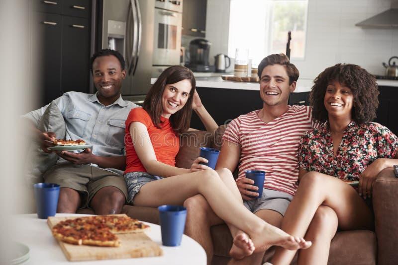 Jonge volwassen vrienden die op TV met voedsel en dranken thuis letten stock fotografie
