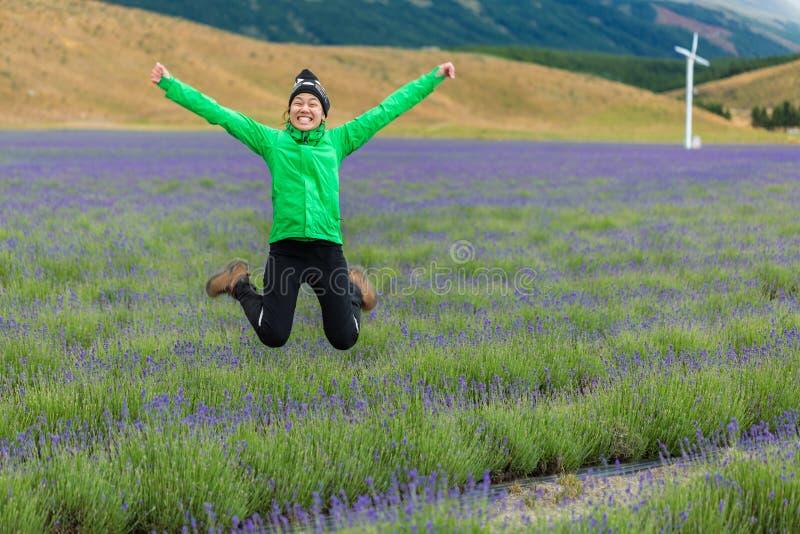 Jonge volwassen vrouw die op lavendelgebied springen royalty-vrije stock foto