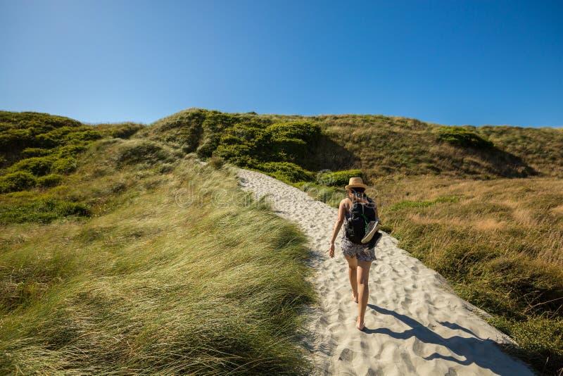 Jonge volwassen vrouw die op zandspoor bij Wharariki-Strand lopen stock foto's