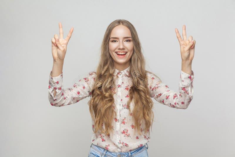 Jonge volwassen vrouw die vredesteken en het toothy glimlachen tonen stock foto's