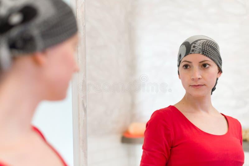 Jonge volwassen vrouwelijke kankerpatiënt die headscarf het kijken in de spiegel dragen Vermoeide, uitgeputte patiënt stock afbeelding