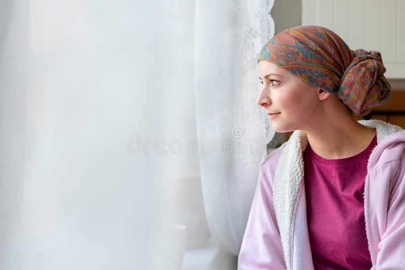 Jonge volwassen vrouwelijke kankerpatiënt headscarf en badjaszitting die in de keuken dragen royalty-vrije stock foto's