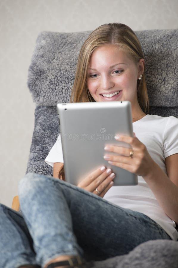 Jonge volwassen vrouwelijke lezing op een tabletPC stock foto's