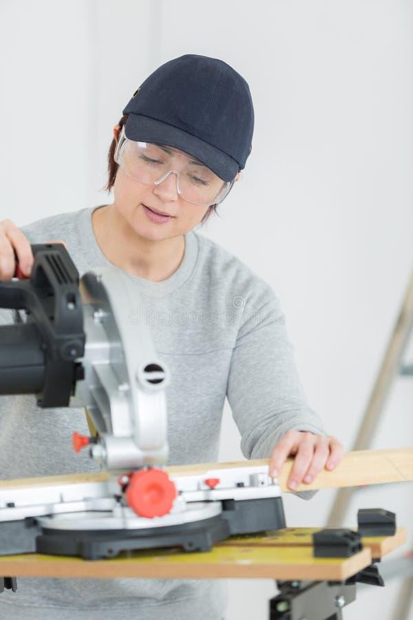 Jonge volwassen vrouwelijke schrijnwerker scherpe raad in workshop stock afbeelding