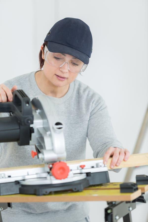 Jonge volwassen vrouwelijke schrijnwerker scherpe raad in workshop royalty-vrije stock afbeeldingen