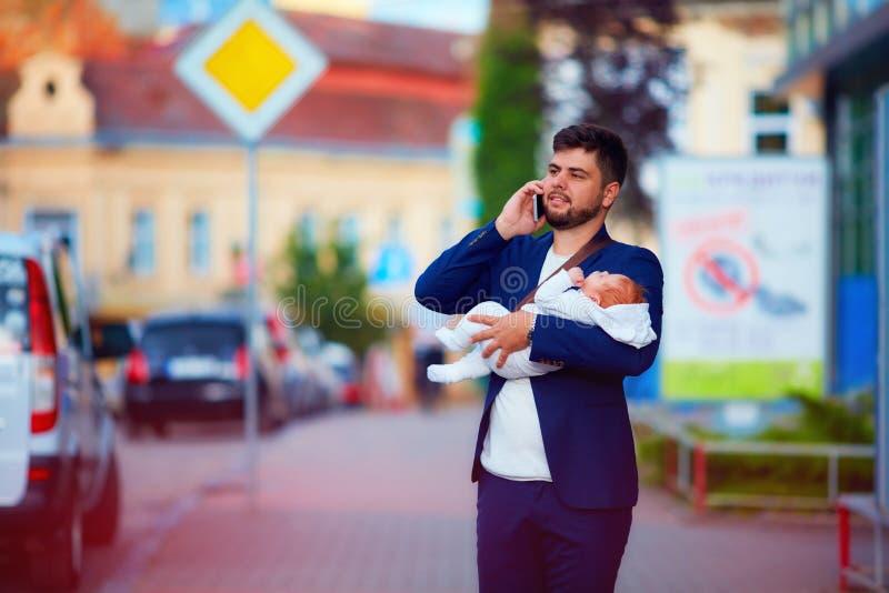 Jonge volwassen zakenman die door de stad met pasgeboren baby op handen lopen royalty-vrije stock afbeeldingen