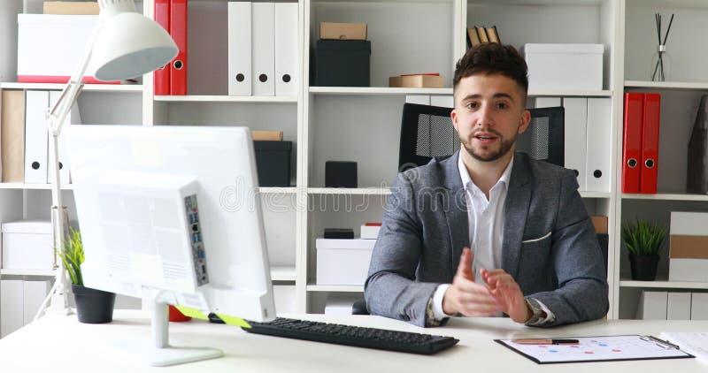 Jonge volwassen zakenman die in werkplaats camera in modern bureau bekijken stock foto's