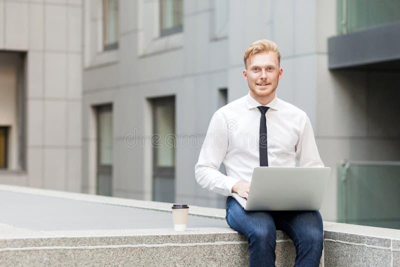 Jonge volwassen zakenman het werk delocalisering, bekijkend camera en toothy glimlach stock foto