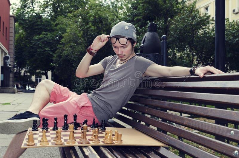 Jonge volwassen zitting op een een bank en het spelen schaak royalty-vrije stock foto's