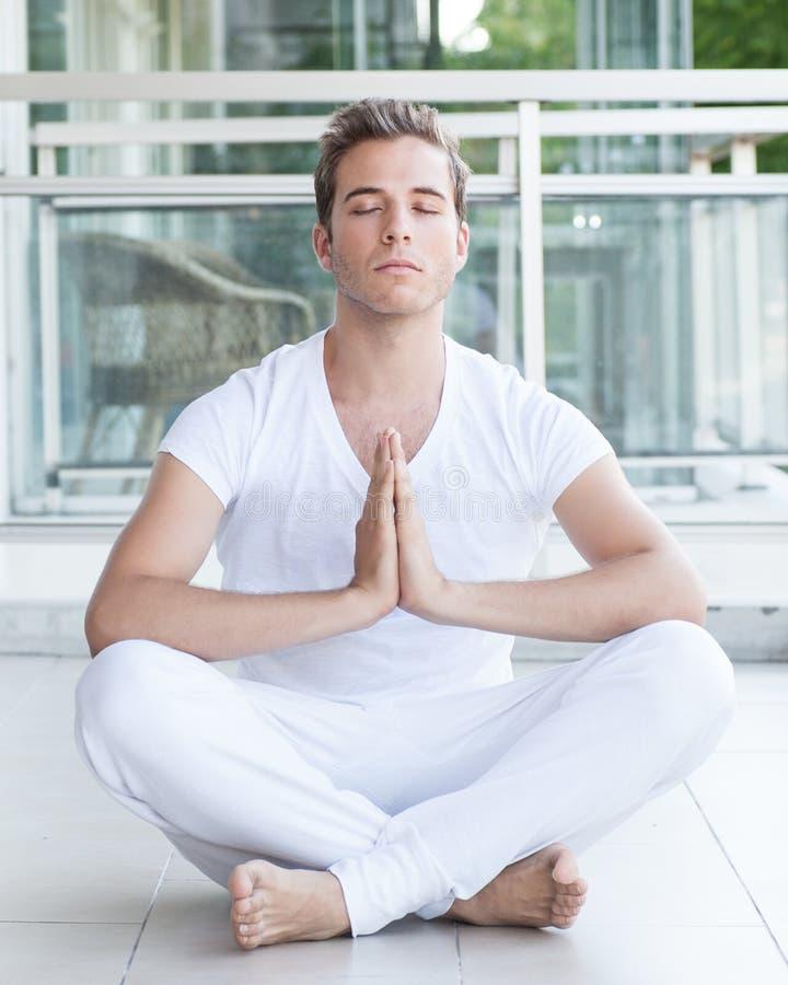 Jonge volwassene die met handen samen mediteren royalty-vrije stock foto's
