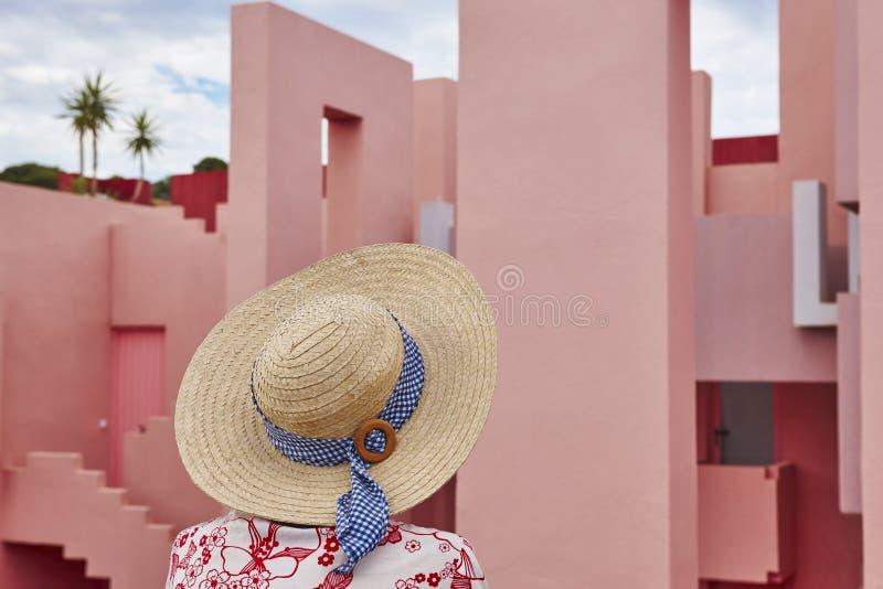 Jonge volwassenen Vrouw met roze geometrische de bouwachtergrond Het ontspannen royalty-vrije stock fotografie