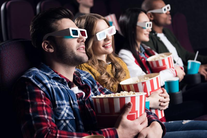 jonge vrienden in 3d glazen met popcorn en soda het letten op film stock afbeelding