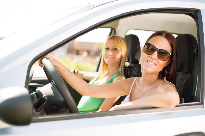 Jonge vrienden die in auto zitten royalty-vrije stock afbeelding