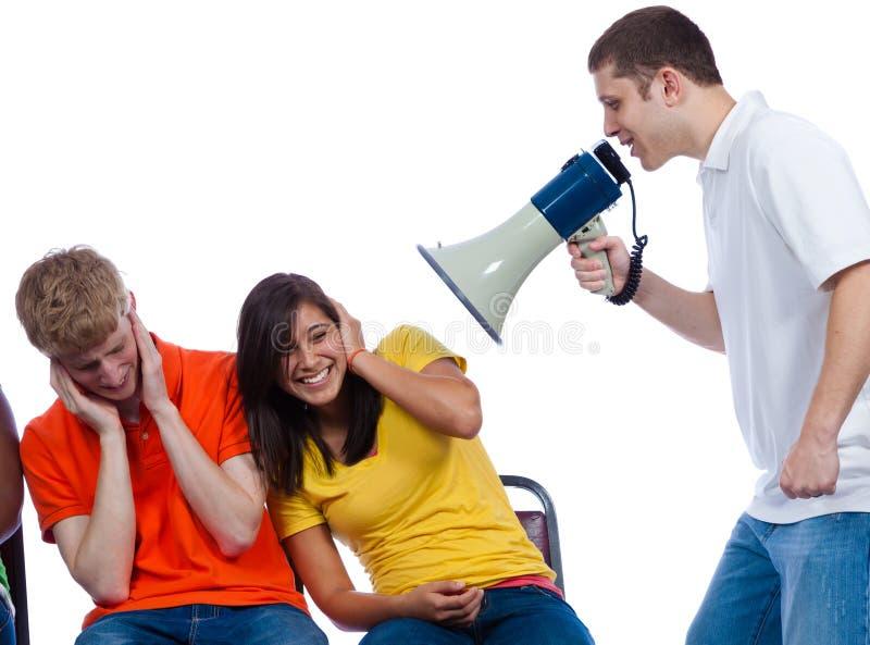 Jonge vrienden die bij door een megafoon worden geschreeuwd stock foto's