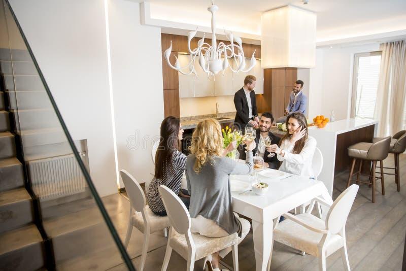Jonge vrienden die diner hebben thuis en met witte wijn roosteren royalty-vrije stock foto's