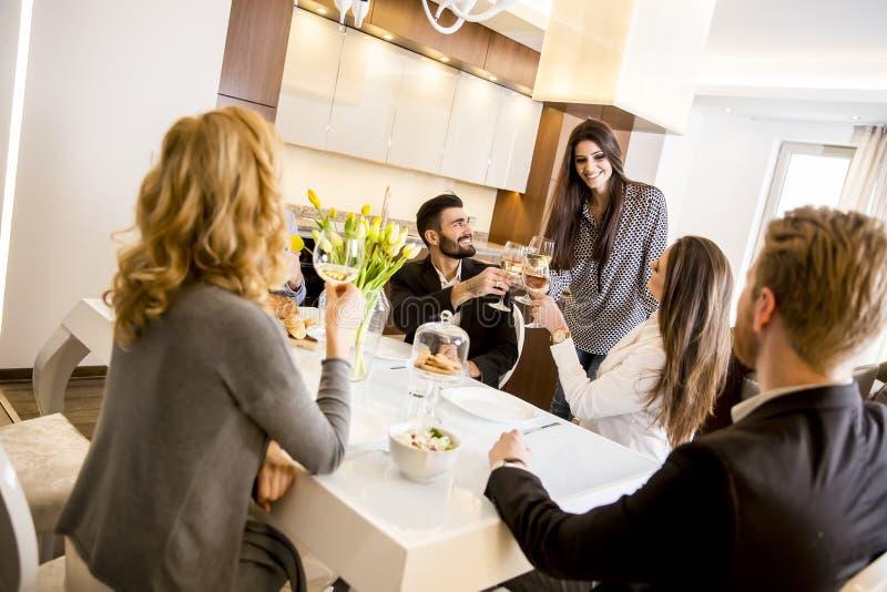 Jonge vrienden die diner hebben thuis en met witte wijn roosteren stock afbeelding