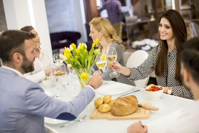 Jonge vrienden die diner hebben thuis en met witte wijn roosteren stock foto