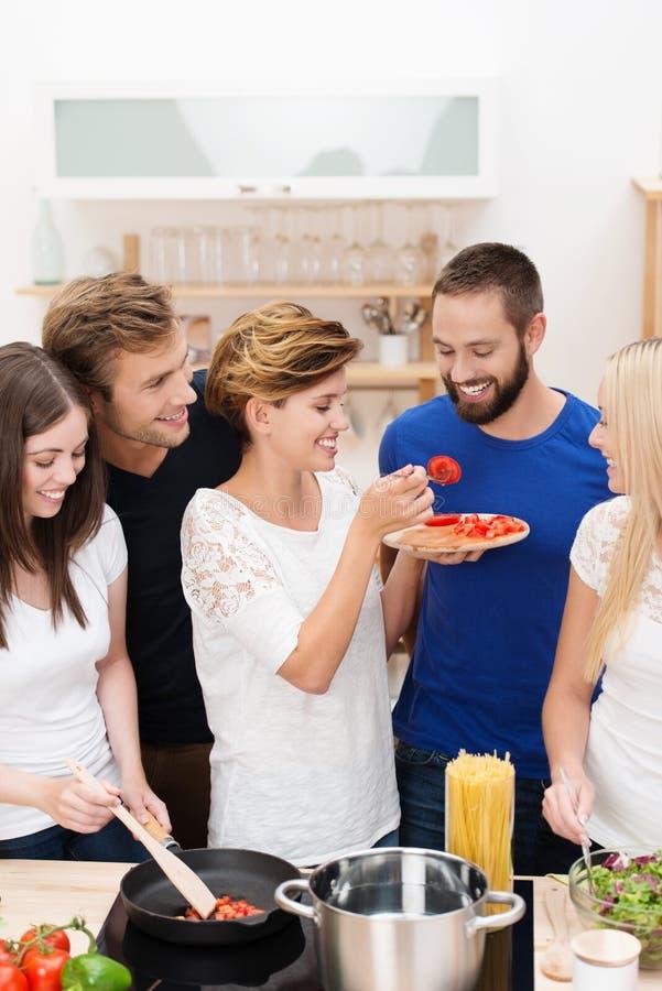 Jonge vrienden die diner samen koken royalty-vrije stock foto