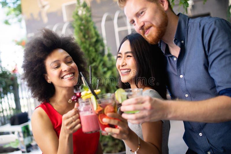 Jonge vrienden die een grote tijd hebben samen Groep en mensen die spreken glimlachen royalty-vrije stock afbeeldingen