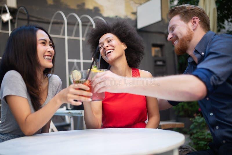 Jonge vrienden die een grote tijd hebben samen Groep en mensen die spreken glimlachen stock afbeeldingen