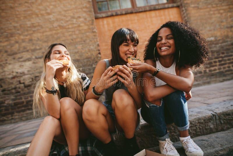 Jonge vrienden die op de stoep zitten en pizza hebben royalty-vrije stock foto's