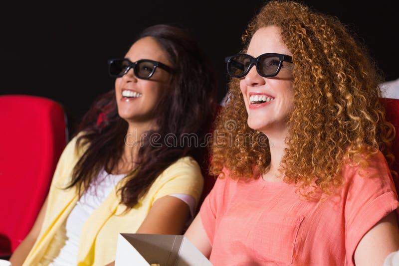 Jonge vrienden die op een 3d film letten stock foto