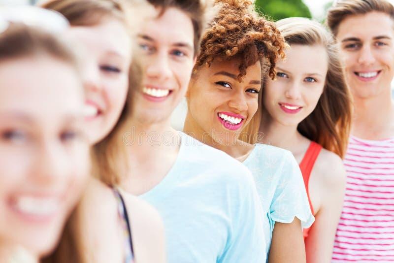 Jonge vrienden die op een rij glimlachen royalty-vrije stock afbeeldingen