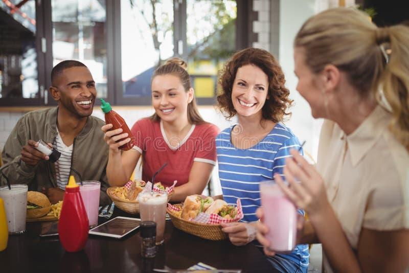 Jonge vrienden die terwijl het zitten bij koffie spreken royalty-vrije stock foto