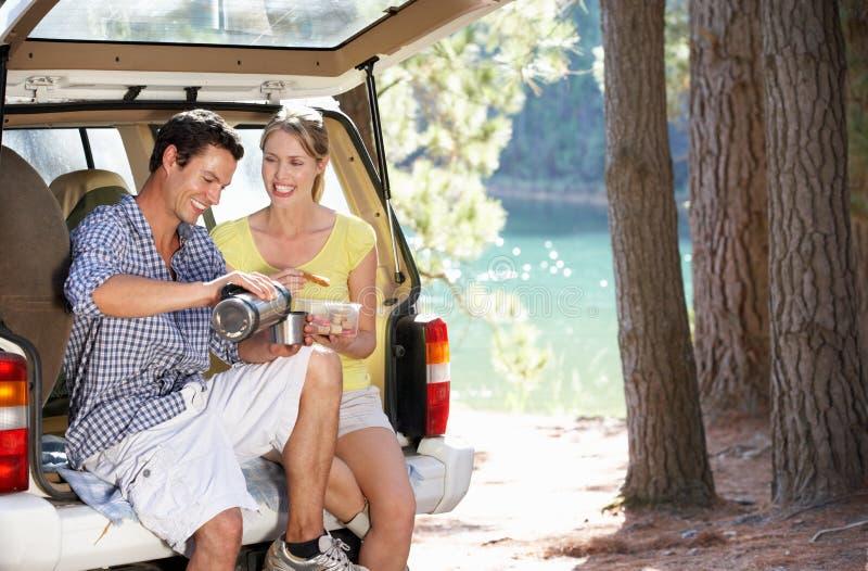 Jonge vrienden die van een picknick genieten door het water royalty-vrije stock foto