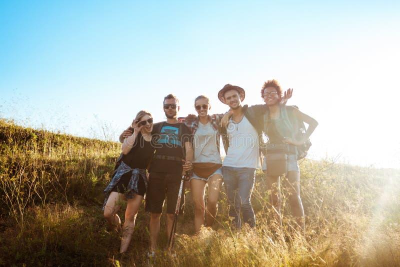 Jonge vrienden die, zich verheugt, bekijkend camera, die in gebied bevinden glimlachen zich royalty-vrije stock fotografie