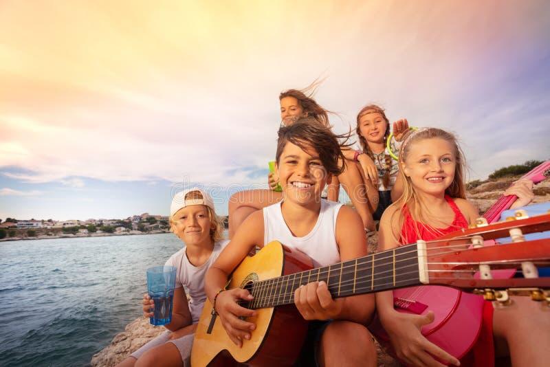 Jonge vrienden met gitaar die pret hebben in openlucht stock foto's