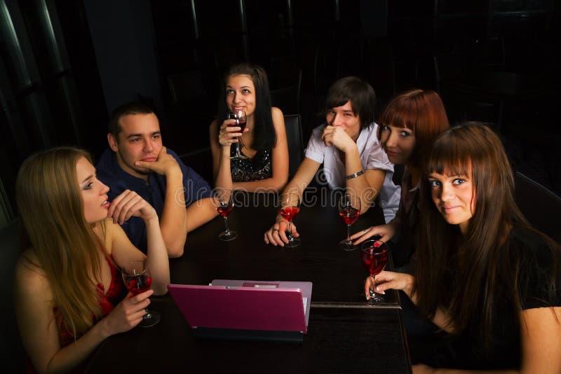 Jonge vrienden met laptop in een staaf. stock foto's