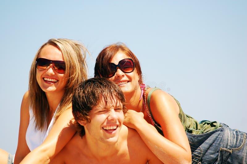 Jonge vrienden op het de zomerstrand stock fotografie