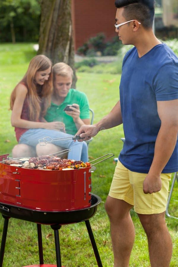 Jonge vrienden tijdens barbecue royalty-vrije stock afbeelding