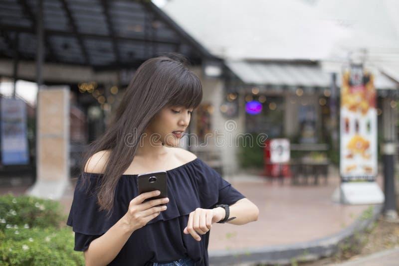 Jonge vrij Aziatische smartphone van de vrouwenholding en het bekijken polshorloge stock foto