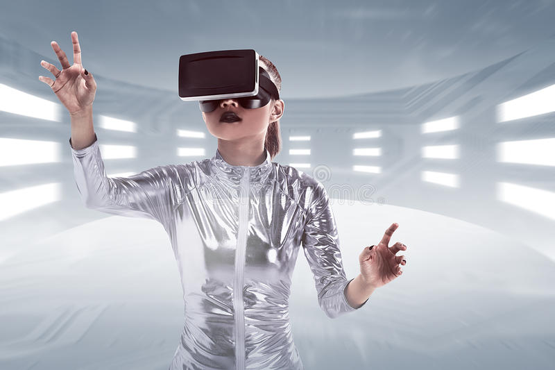 Jonge vrij Aziatische vrouw die VR-hoofdtelefoon binnen virtuele wereld dragen stock afbeelding