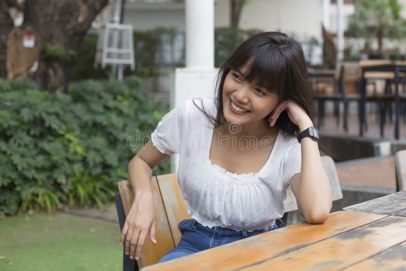Jonge vrij Aziatische vrouwenzitting in openluchtrestaurant royalty-vrije stock fotografie