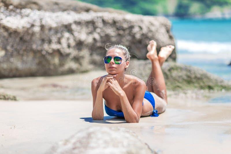 Jonge vrij blonde vrouw in blauwe bikini op wit tropisch strand stock afbeeldingen