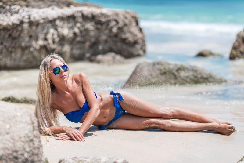 Jonge vrij blonde vrouw in blauwe bikini op wit tropisch strand stock foto