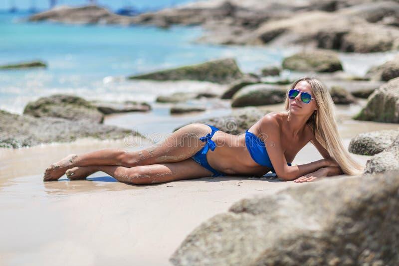 Jonge vrij blonde vrouw in blauwe bikini op wit tropisch strand stock afbeelding