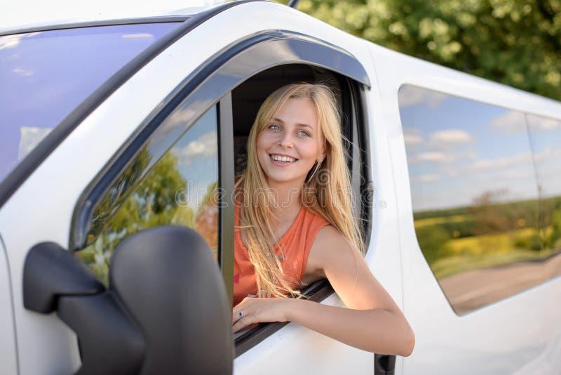 Jonge vrij blonde vrouw die witte auto drijven en royalty-vrije stock foto's