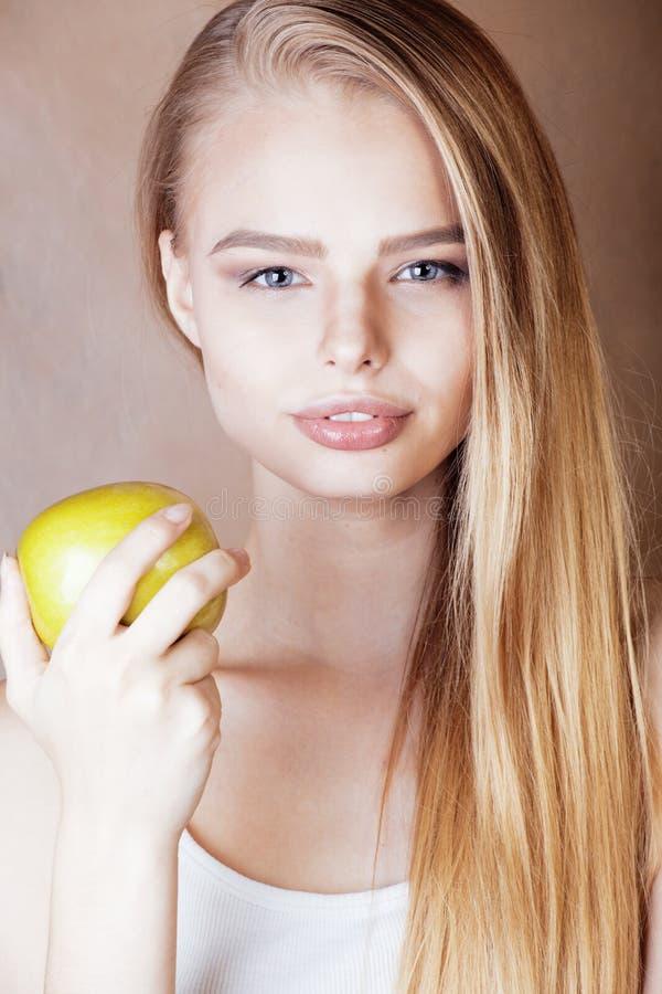 Jonge vrij blonde vrouw met het groene appel gelukkige vrolijke glimlachen dicht omhoog op warme bruine achtergrond, levensstijlm royalty-vrije stock afbeelding