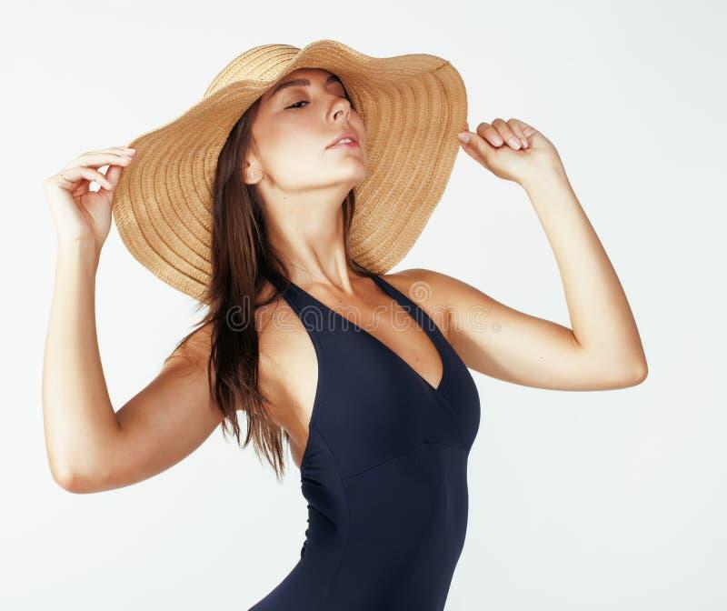 Jonge vrij donkerbruine vrouw de zomerhoed dragen en zwempak die op witte achtergrond wordt geïsoleerd die die aan vakanties voor stock foto's